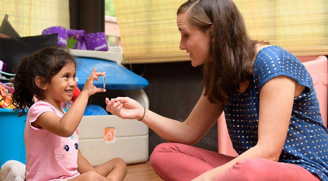 child having fun with speech therapist