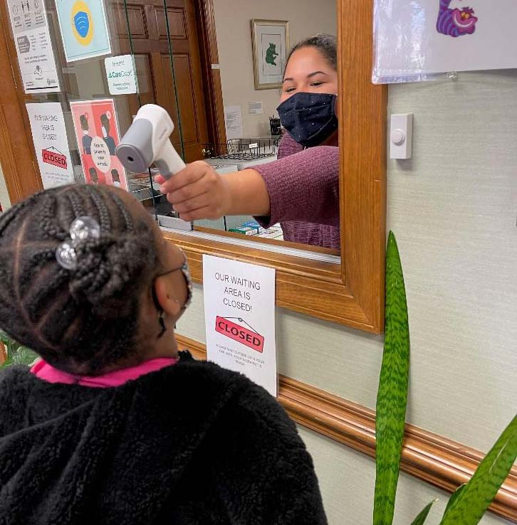 Patient having temperature taken at check-in window