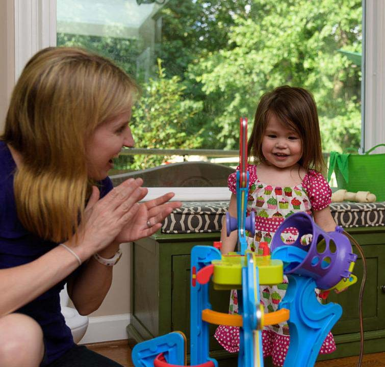 young girl receiving speech therapy at home playing with toys